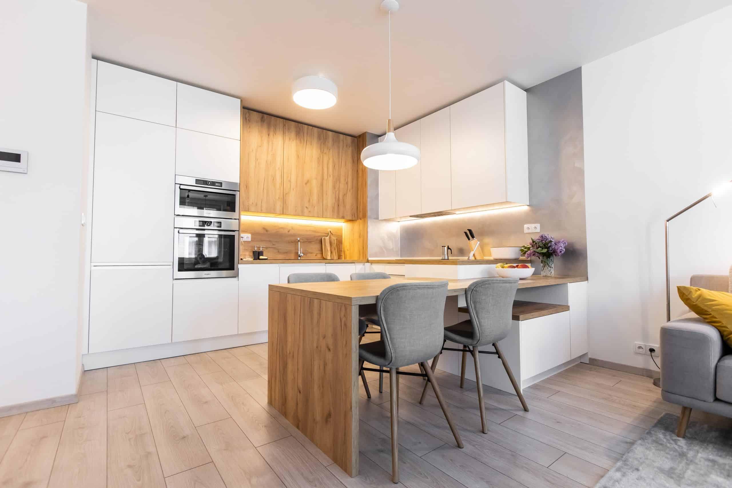Biela kuchyna s drevom a so stolom