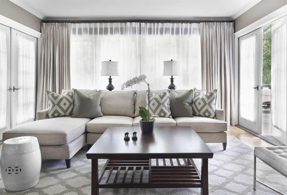 sivá rohová sedačka v obývačke so závesmi