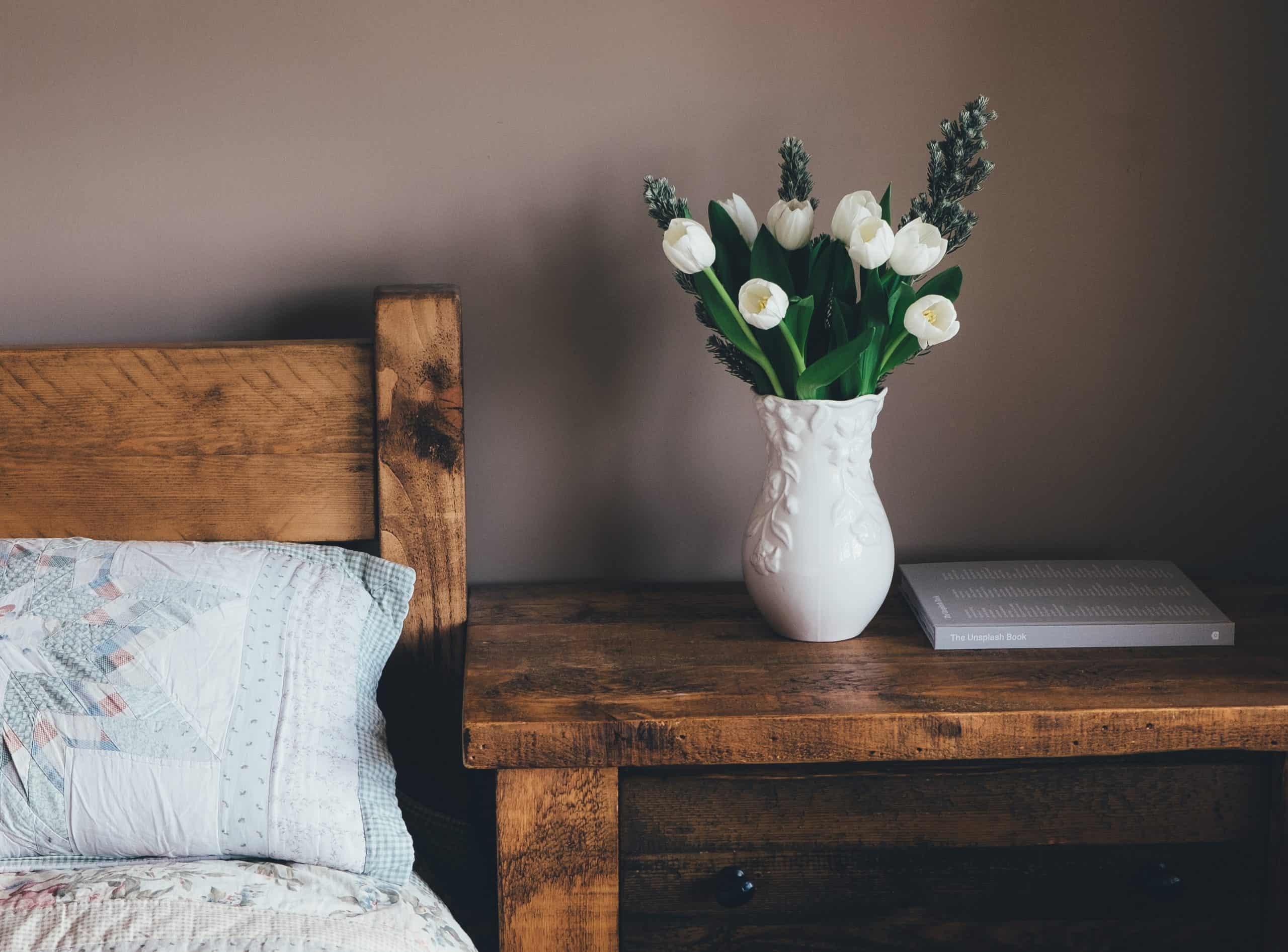 drevený nábytok v spálni s kyticou