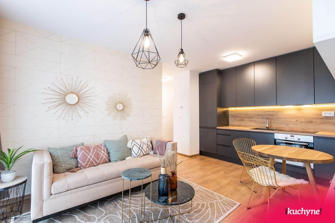 V tejto realizácii 2,5–izbového bytu v Urban Residence boli použité viaceré oblé kúsky. Či už je to jedálenský alebo konferenčný stolík, stolík pod kvet, aj stoličky majú zaoblené tvary, ale aj výrazná ozdoba nad sedačkou. Zdroj: iKuchyne.sk