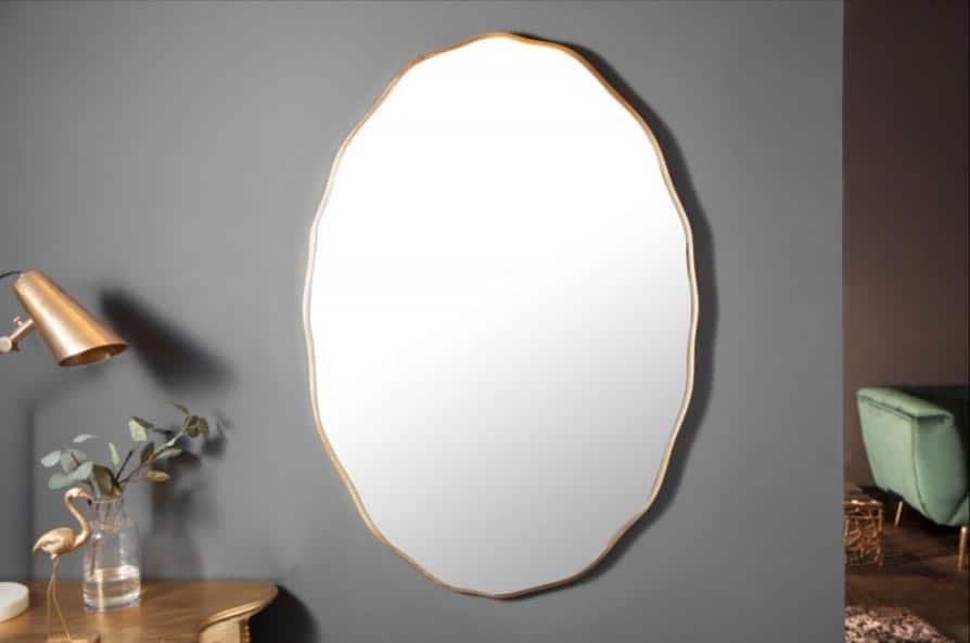 Aj oválne zlaté zrkadlo rozžiari biely interiér. Zdroj: iKuchyne.sk