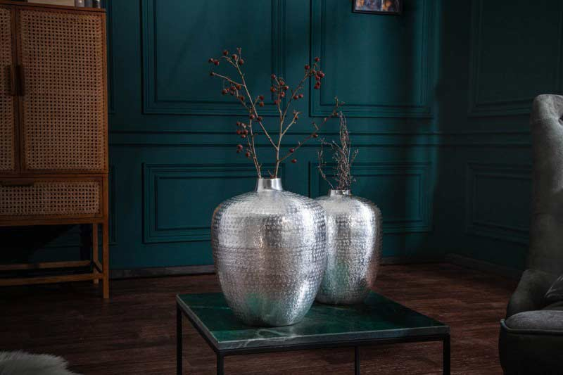 Kovová váza, textilná sedačka a drevené skrinky vytvárajú štýlovú obývačku. Zdroj: iKuchyne.sk